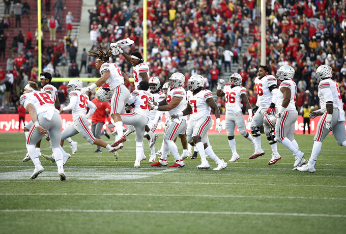 Ohio State players run onto the field to celebrate after an NCAA football game against Maryland, Saturday, Nov. 17, 2018, in College Park, Md. Ohio State won 52-51 in overtime. (AP Photo/Nick Wass)