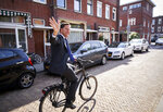 Netherlands Prime Minister Mark Rutte leaves on his bike after voting in the European elections in The Hague, Netherlands, Thursday, May 23, 2019. (AP Photo/Phil Nijhuis)