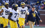 "FILE- In an April 13, 2019, file photo, Michigan head coach Jim Harbaugh walks out with players during the team's annual spring NCAA college football game in Ann Arbor, Mich. Harbaugh seems to be set up for success at Michigan in his fifth season, leading a program that is a popular choice to win the Big Ten. ""That's where I would pick us,"" Harbaugh said. Some are predicting the Wolverines will earn a spot in the College Football Playoff to give them a chance to win a national championship for the first time since 1997. (AP Photo/Carlos Osorio, File)"