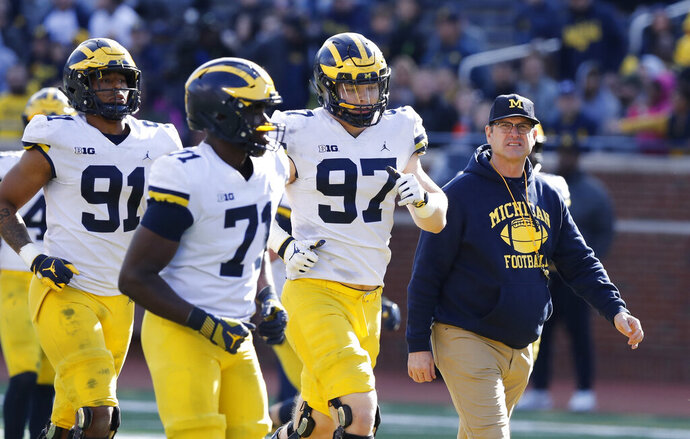 FILE- In an April 13, 2019, file photo, Michigan head coach Jim Harbaugh walks out with players during the team's annual spring NCAA college football game in Ann Arbor, Mich. Harbaugh seems to be set up for success at Michigan in his fifth season, leading a program that is a popular choice to win the Big Ten.