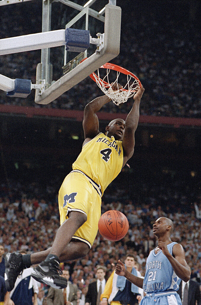 FILE - In this April 5, 1993, file photo, Michigan's Chris Webber hangs from the rim after dunking the ball during the NCAA Final Four championship game against North Carolina at the Superdome in New Orleans. North Carolina defeated Michigan, 77-71. (AP Photo/Ed Reinke, File)