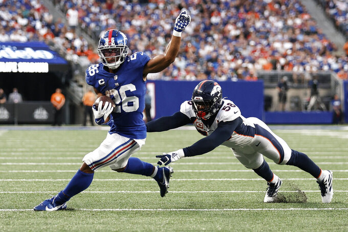 New York Giants running back Saquon Barkley (26) runs away from Denver Broncos' Von Miller (58) during the second half of an NFL football game Sunday, Sept. 12, 2021, in East Rutherford, N.J. The Broncos won 27-13. (AP Photo/Adam Hunger)