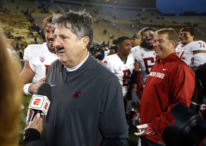 Washington State head coach Mike Leach wears a fake mustache placed on him by starting quarterback Gardner Minshew, back, during a television interview after an NCAA college football game against Colorado Saturday, Nov. 10, 2018, in Boulder, Colo. Washington State won 31-7. (AP Photo/David Zalubowski)