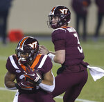 Virginia Tech's Khalil Herbert, left, takes a handoff from quarterback Braxton Burmeister during the first half of the team's NCAA college football game against Virginia on Saturday, Dec. 12, 2020, in Blacksburg, Va. (Matt Gentry/The Roanoke Times via AP, Pool)