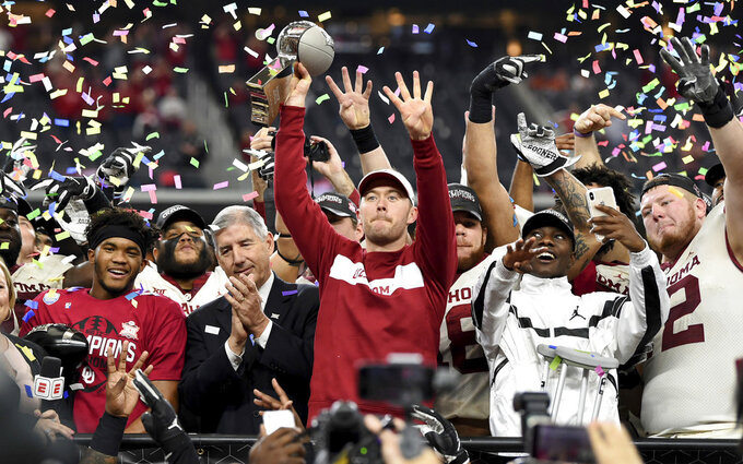 Oklahoma head coach Lincoln Riley hoists the Big 12 Conference championship trophy after beating Texas 39-27 in the Big 12 Conference championship NCAA college football game on Saturday, Dec. 1, 2018, in Arlington, Texas. (AP Photo/Jeffrey McWhorter)