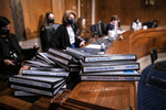 Folders detailing the COVID vaccine plans for states are stacked on a table during a confirmation hearing for Secretary of Health and Human Services nominee Xavier Becerra before the Senate Health, Education, Labor and Pensions Committee, Tuesday, Feb. 23, 2021 on Capitol Hill in Washington. (Sarah Silbiger/Pool via AP)