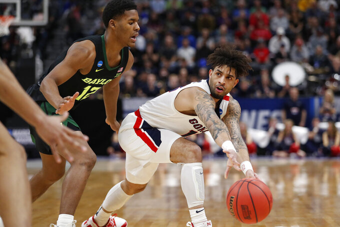 Gonzaga guard Josh Perkins, right, passes the ball against Baylor guard Jared Butler (12) during the first half of a second-round game in the NCAA men's college basketball tournament Saturday, March 23, 2019, in Salt Lake City. (AP Photo/Jeff Swinger)