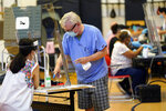 A voter, right, signs with a covered finger before voting Tuesday, July 14, 2020, in Houston. (AP Photo/David J. Phillip)
