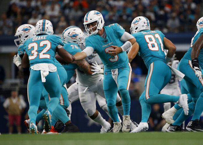 Miami Dolphins running back Kenyan Drake (32) takes the handoff from quarterback Josh Rosen (3) in the first half of a NFL football game against the Dallas Cowboys in Arlington, Texas, Sunday, Sept. 22, 2019. (AP Photo/Ron Jenkins)