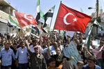 FILE - This September 14, 2018 file photo, protesters wave revolutionary Syrian and Turkish flags as they attend a demonstration against the Syrian government offensive in Idlib, in Maarat al-Numan, south of Idlib, Syria. n two months of intensive airstrikes and bombardments on the rebel-controlled province of Idlib, Syrian government forces and their Russian allies have failed to make progress against battle-hardened insurgents. (Ugur Can/DHA via AP, File)