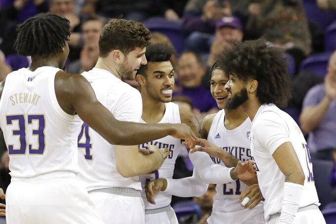 Washington's Isaiah Stewart (33), Sam Timmins, Jamal Bey, RaeQuan Battle and Marcus Tsohonis smile as they huddle after a score against Stanford in the first half of an NCAA college basketball game Thursday, Feb. 20, 2020, in Seattle. (AP Photo/Elaine Thompson)