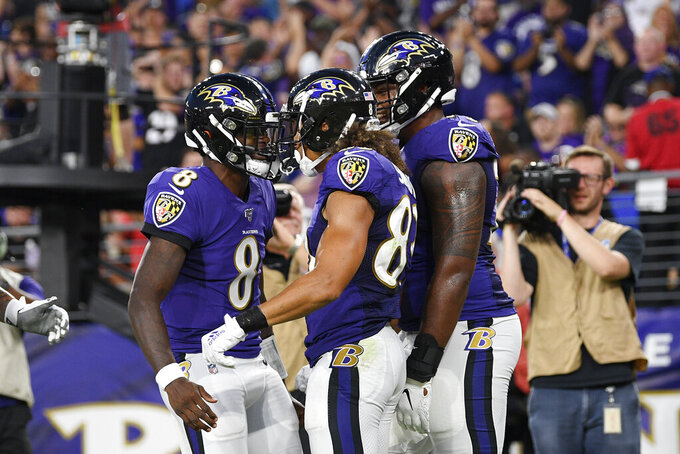 Baltimore Ravens quarterback Lamar Jackson (8) and wide receiver Willie Snead (83) celebrate after they connected for a touchdown against the Jacksonville Jaguars during the first half of an NFL football preseason game Thursday, Aug. 8, 2019, in Baltimore. (AP Photo/Nick Wass)
