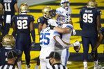 BYU running back Tyler Allgeier (25) celebrates with offensive lineman Clark Barrington (56) after scoring a touchdown during the second half of an NCAA college football game against Navy, Monday, Sept. 7, 2020, in Annapolis, Md. (AP Photo/Tommy Gilligan)