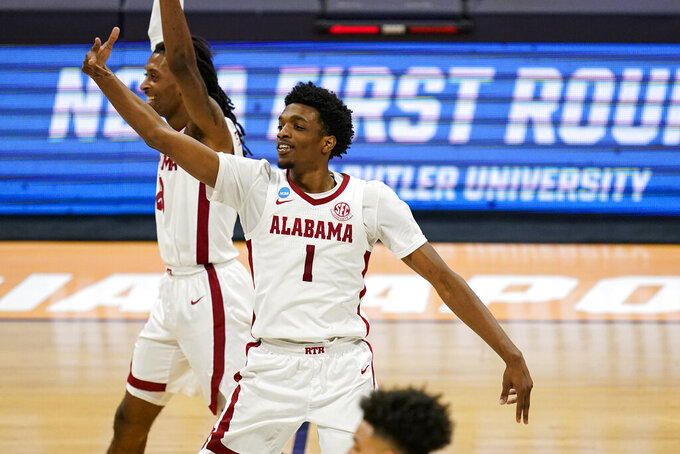 Alabama forward Herbert Jones (1) celebrates in the second half of a first-round game against Iona in the NCAA men's college basketball tournament at Hinkle Fieldhouse in Indianapolis, Saturday, March 20, 2021. Alabama defeated Iona 68-55. (AP Photo/Michael Conroy)