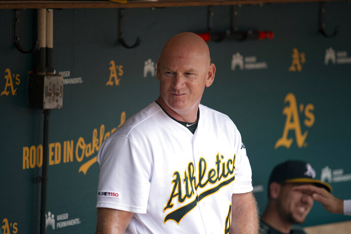 """FILE - In this Sept. 22, 2019, file photo, Oakland Athletics third base coach Matt Williams is shown in the dugout before a baseball game against the Texas Rangers in Oakland, Calif.  Back managing a team, just being able to talk with his players is a challenge for Matt Williams. About 10 miles from the spring training camps of the Boston Red Sox and Minnesota Twins, the 54-year-old is at spring training with South Korea's Kia Tigers. """"You never know whether you're going to get another chance to manager or not, so I look at it as a challenge or an opportunity,'' he said, sitting in some small metal bleachers. """"So far it's been a lot of fun."""" (AP Photo/D. Ross Cameron, File)"""