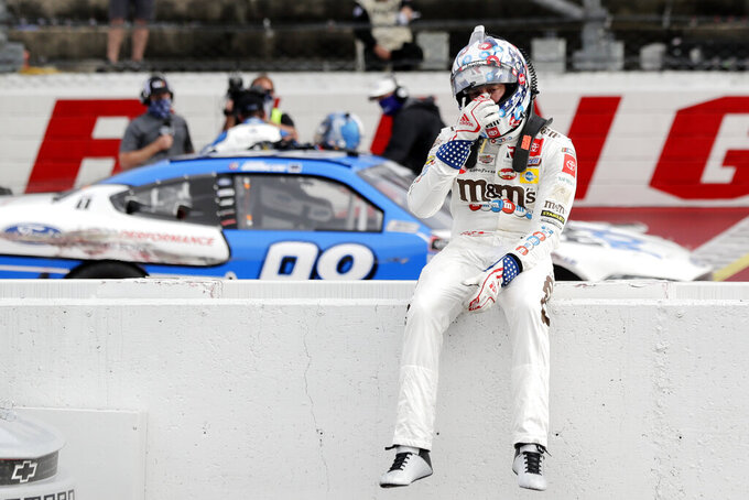 Kyle Busch sits on the wall as Chase Briscoe celebrates behind him after Briscoe edged out Busch to win the NASCAR Xfinity series auto race Thursday, May 21, 2020, in Darlington, S.C. (AP Photo/Brynn Anderson)