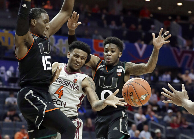 Virginia Tech's Nickeil Alexander-Walker (4) passes the ball as Miami's Ebuka Izundu (15) and Chris Lykes (0) defend during the second half of an NCAA college basketball game in the Atlantic Coast Conference tournament in Charlotte, N.C., Wednesday, March 13, 2019. (AP Photo/Nell Redmond)