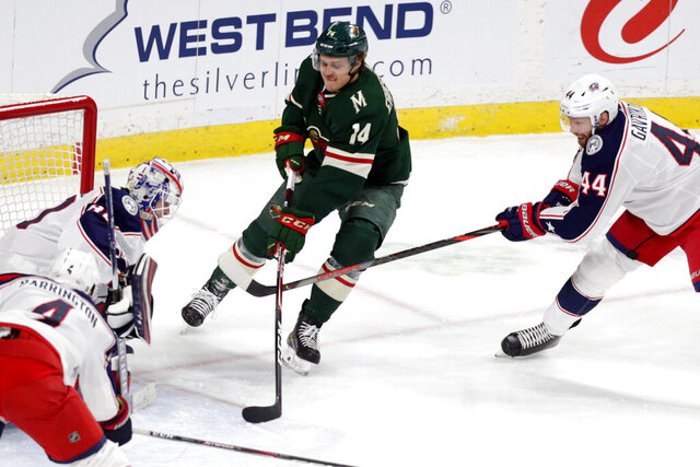 Minnesota Wild center Joel Erikssson Ek (14) shoots on Columbus Blue Jackets goalie Matiss Kivlenieks (80) and Columbus Blue Jackets defenseman Vlakislav Gavrikov (44) during the first period of an NHL hockey game Tuesday, Feb. 25, 2020, in St. Paul, Minn. (AP Photo/Andy Clayton-King)