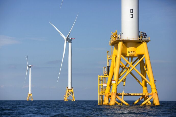 FILE - In this Monday, Aug. 15, 2016 file photo, three of Deepwater Wind's turbines stand in the water off Block Island, R.I. The state approved tax credits on Monday, Aug. 26, 2019, to lure Boston Energy, a third major offshore wind company, to the state. Rhode Island Gov. Gina Raimondo announced in June 2019 that British wind turbine maintenance company, GEV, will locate its U.S. headquarters in the state. The Danish offshore wind company Orsted operates Deepwater Wind. (AP Photo/Michael Dwyer, File)