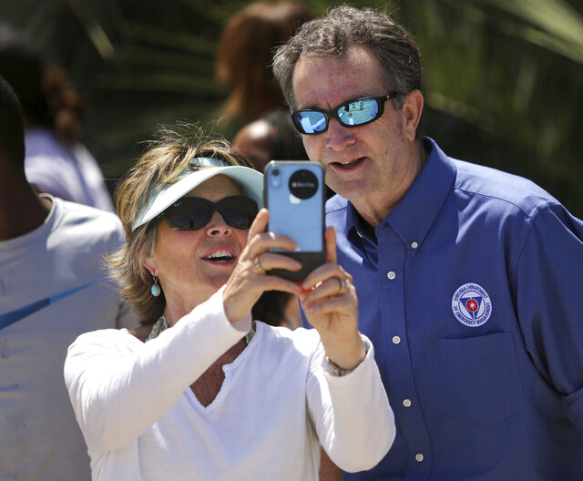 In this Saturday, May 23, 2020, photo, Gov. Ralph Northam and Tori Bloxom, of Onancock, Va., take a selfie as the governor visits the Oceanfront in Virginia Beach, Va., to see for himself how crowded the beach was. Northam has repeatedly urged Virginia residents to cover their faces in public during the COVID-19 pandemic, but the Democrat didn't heed his own plea when he posed mask-less for photographs alongside residents during the weekend beach visit. A spokeswoman for the governor's office said on Sunday that Northam should have brought a face mask with him during his visit on Saturday to the Virginia Beach Oceanfront. (Stephen M. Katz/The Virginian-Pilot via AP)