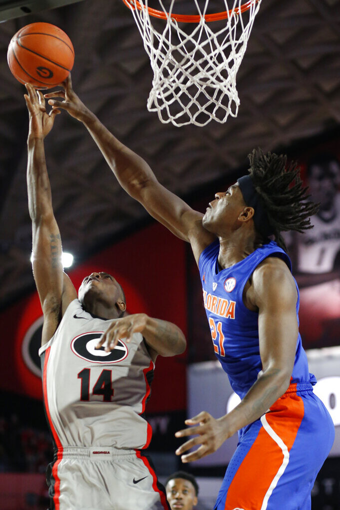 Florida forward Dontay Bassett (21) blocks a shot from Georgia guard Tye Fagan (14)  during an NCAA college basketball game in Athens, Ga., on Saturday, Jan. 19, 2019.  ( Joshua L. Jones/Athens Banner-Herald via AP)