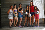 Soccer player Mara Gomez, second from right, poses with her soccer loving family members at their home in La Plata, Argentina, Thursday, Feb. 6, 2020. From left are her mother Carolina Cardozo, sisters Keila, Evelin holding daughter Kima, Kiara and Yamila. Gomez is a transgender woman who is limited to only training with her women's professional soccer team, Villa San Carlos. She is waiting for confirmation from the Argentina Football Association (AFA) she can play. (AP Photo/Natacha Pisarenko)