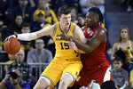 Michigan center Jon Teske, left, is guarded by Nebraska forward Yvan Ouedraogo during the first half of an NCAA college basketball game Thursday, March 5, 2020, in Ann Arbor, Mich. (AP Photo/Jose Juarez)