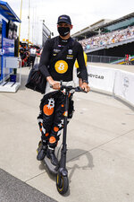 Rinus VeeKay of the Netherlands rides his scooter out of the pit area during practice for the Indianapolis 500 auto race at Indianapolis Motor Speedway in Indianapolis, Friday, May 21, 2021. (AP Photo/Michael Conroy)