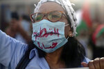 A woman wearing a face mask to prevent the spread of coronavirus chants slogans during a protest against normalizing relations with Israel, in Rabat, Morocco, Friday, Sept. 18, 2020. Despite a government ban on large gatherings aimed at preventing the spread of the coronavirus, scores of Moroccans staged a protest outside parliament building in the capital Rabat on Friday to denounce Arab normalization agreements with Israel. The words on the masks read