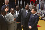 Ivory Coast's Prime Minister Amadou Gon Coulibaly, center-right, stands next to France's President Emmanuel Macron, right, during the French President's visit to the country, in the Koumassi suburb of Abidjan, Ivory Coast Saturday, Dec. 21, 2019. Ivory Coast's Prime Minister Amadou Gon Coulibaly, the presidential candidate of Ivory Coast's ruling party, died Wednesday, July 8, 2020 just days after returning from two months of medical treatment in France, where he previously had undergone a heart transplant, the country's presidency announced. (AP Photo/Diomande Ble Blonde)