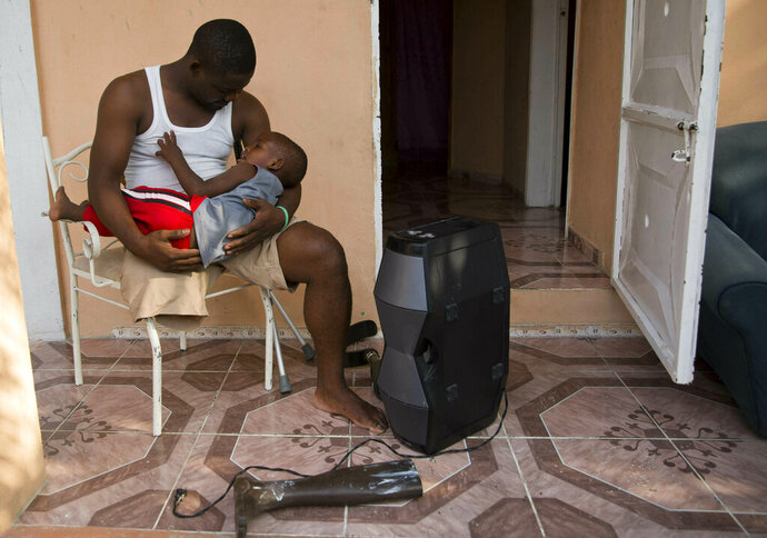 In this June 5, 2019 photo, prosthetic technician Wilfrid Macena cradles his son Wilensky while sitting on their front porch in Carrefour, Haiti. Macena was a welder who built gas station tanks for a living when the devastating 2010 earthquake toppled a wall at the garage where he worked and crushed his right leg. (AP Photo/Dieu Nalio Chery)
