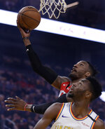 Houston Rockets' Robert Covington lays up a shot over Golden State Warriors' Andrew Wiggins during the first half of an NBA basketball game Thursday, Feb. 20, 2020, in San Francisco. (AP Photo/Ben Margot)