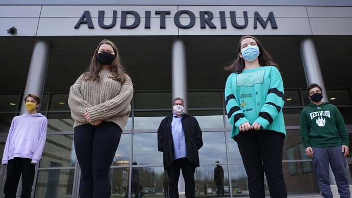 While wearing protective masks due to the COVID-19 outbreak, Jim Howard, a drama teacher at Westwood, Mass., High School, center, poses with his student actors outside the school's auditorium after working on their virtual performance of Shakespeare's