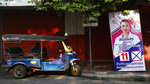 In this March 15, 2019, photo, a tuk-tuk driver waits for customers beside an election campaign poster in Bangkok, Thailand. Thailand heads to the polls Sunday, March 24, 2019 to vote in the country's first general election since the military toppled an elected government in a coup nearly five years ago. (AP Photo/Sakchai Lalit)