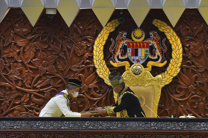 In this photo released by Malaysia's Department of Information, Malaysia's King Sultan Abdullah Sultan Ahmad Shah, right, receives documents from Prime Minister Muhyiddin Yassin during the opening ceremony of the third term of the 14th parliamentary session at parliament house in Kuala Lumpur Monday, May 18, 2020. Malaysia's King on Wednesday, June 16, 2021, said that Parliament, which has been suspended under a coronavirus emergency since January, must resume as soon as possible. (Nazri Rapai/Malaysia's Department of Information via AP)