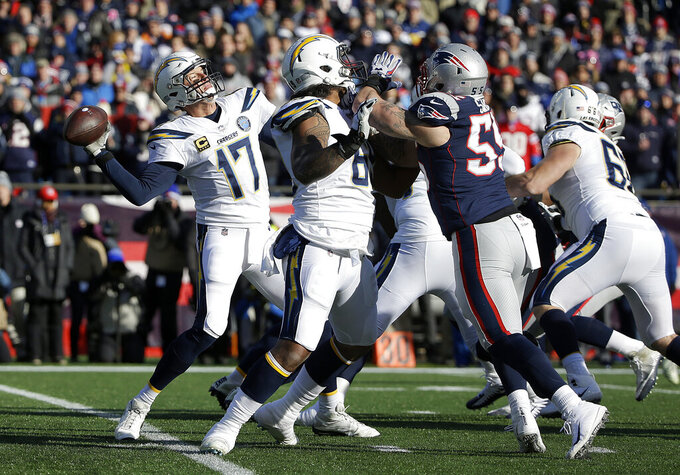 Los Angeles Chargers quarterback Philip Rivers passes under pressure from New England Patriots defensive end John Simon (55) during the first half of an NFL divisional playoff football game, Sunday, Jan. 13, 2019, in Foxborough, Mass. (AP Photo/Steven Senne)