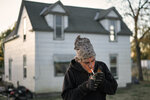 In this Tuesday, Oct. 22, 2019 photo, Marty Study lights a cigarette in front of his flood-damaged home in Bartlett, Iowa. Study has lived in a trailer since the March floods and had to be rescued from a second-floor window when his house flooded. Flooding along the Missouri River has stretched on for seven months in places and could endure through the winter, leaving some Upper Midwest farmland and possibly some homes encased in ice.  (AP Photo/Nati Harnik)