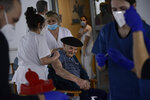Alejandro Nemoues, a resident at Ibaneta nursing home, is vaccinated with Pfizer coronavirus vaccine, in Erro, around 35 kms (21miles) from Pamplona, northern Spain, Tuesday Jan. 5, 2021. Spain plans to receive over 4.5 million doses of the vaccine over the next three months, enough it says to immunize just over 2.2 million people. The government estimates that this first phase will be enough to cover nursing home residents and workers, followed by health workers in general and people with disabilities. (AP Photo/Alvaro Barrientos)