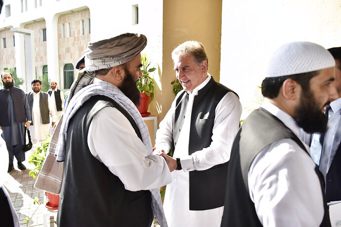 In this photo released by the Foreign Office, Pakistan's Foreign Minister Shah Mehmood Qureshi, center, receives members of Taliban delegation at the Foreign Office in Islamabad, Pakistan, Thursday, Oct. 3, 2019. Senior Taliban leaders are meeting with Qureshi in Islamabad as part of a push to revive an Afghanistan peace deal that has included stops in Russia, China and Iran. (Pakistan Foreign Office via AP)