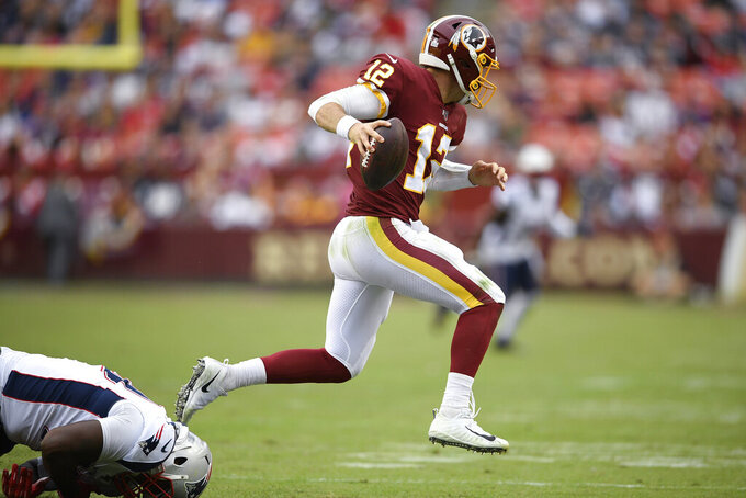 Washington Redskins quarterback Colt McCoy (12) runs against the New England Patriots during the second half of an NFL football game, Sunday, Oct. 6, 2019, in Washington. (AP Photo/Nick Wass)