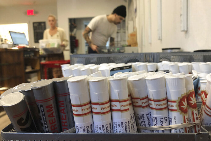 FILE - In this Sept. 20, 2019 file photo, employees at the marijuana retailer Bridge City Collective in Portland, Ore., can be seen setting up the store for the day behind a row of marijuana products for sale there. Michigan has temporarily halted the sale of marijuana products intended for vaping so that they can be tested for a compound linked to lung illnesses. The Marijuana Regulatory Agency issued the emergency rules Friday, Nov. 22, 2019. (AP Photo/Gillian Flaccus File)