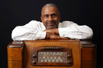 Tavis Smiley, owner of progressive talk radio station KBLA Los Angeles (1580), poses for a portrait on a vintage AM radio in his station's offices, Tuesday, June 15, 2021, in Los Angeles. KBLA's morning drive host Dominique DiPrima gifted Smiley with the radio in celebration of the radio station's launch. (AP Photo/Chris Pizzello)