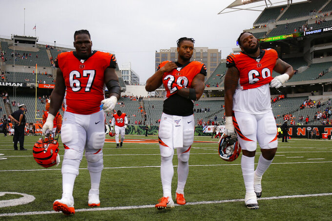File-This Oct. 6, 2019, file photo shows Cincinnati Bengals offensive guard John Miller (67), running back Joe Mixon (28), and offensive tackle Bobby Hart (68) walking off the field after losing an NFL football game against the Arizona Cardinals, in Cincinnati. Pro football had all sorts of newsworthy topics in 2019. Mobile quarterbacks running dynamic offenses should have been the lead item. Or maybe the fact that teams don't tank, as Miami winning four games displays; forget Cincinnati, the Bengals just are that bad.(AP Photo/Gary Landers,File)