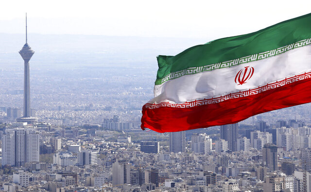 FILE - In this March 31, 2020, file photo, Iran's national flag waves as Milad telecommunications tower and buildings are seen in Tehran, Iran. A British-Australian academic serving a 10-year sentence for espionage in Iran has been moved to a notorious prison where concerns for her well-being have escalated, the Australian government confirmed Wednesday. (AP Photo/Vahid Salemi, File)
