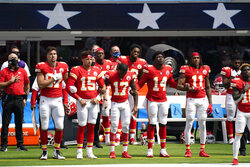 Kansas City Chiefs player lock arms as the national anthem plays before an NFL football game against the Los Angeles Chargers Sunday, Sept. 20, 2020, in Inglewood, Calif. (AP Photo/Ashley Landis )