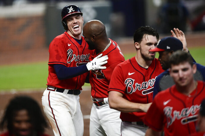 Atlanta Braves' Freddie Freeman, top left, celebrates his winning two-run home with teammates during the 11th inning of a baseball game against the Boston Red Sox, Friday, Sept. 25, 2020, in Atlanta. (AP Photo/John Amis)