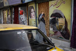 A woman walks past beauty salons with window decorations which have been defaced in Kabul, Afghanistan, Sunday, Sept. 12, 2021. Since the Taliban gained control of Kabul, several images depicting women outside beauty salons have been removed or covered up. (AP Photo/Bernat Armangue)