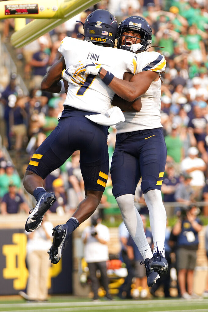 Toledo safety Dequan Finn (7) celebrates a touchdown with teammate Jacquez Stuart in the second half of an NCAA college football game against Notre Dame in South Bend, Ind., Saturday, Sept. 11, 2021. Notre Dame won 32-29. (AP Photo/AJ Mast)