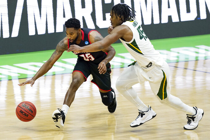 Hartford's Traci Carter (25) drives against Baylor's Davion Mitchell (45) during the first half of a college basketball game in the first round of the NCAA tournament at Lucas Oil Stadium in Indianapolis Friday, March 19, 2021, in Indianapolis, Tenn. (AP Photo/Mark Humphrey)