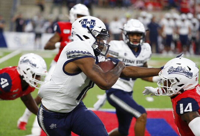 Utah State wide receiver Savon Scarver is stoppped by Fresno State defensive back Jaron Bryant tries to stop him during the first half of an NCAA college football game in Fresno, Calif., Saturday, Nov. 9, 2019. (AP Photo/Gary Kazanjian)